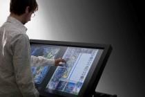 Lo schermo multi-touch del progetto Rerum Novarum e due pagine della Bibbia di Borso d'Este.